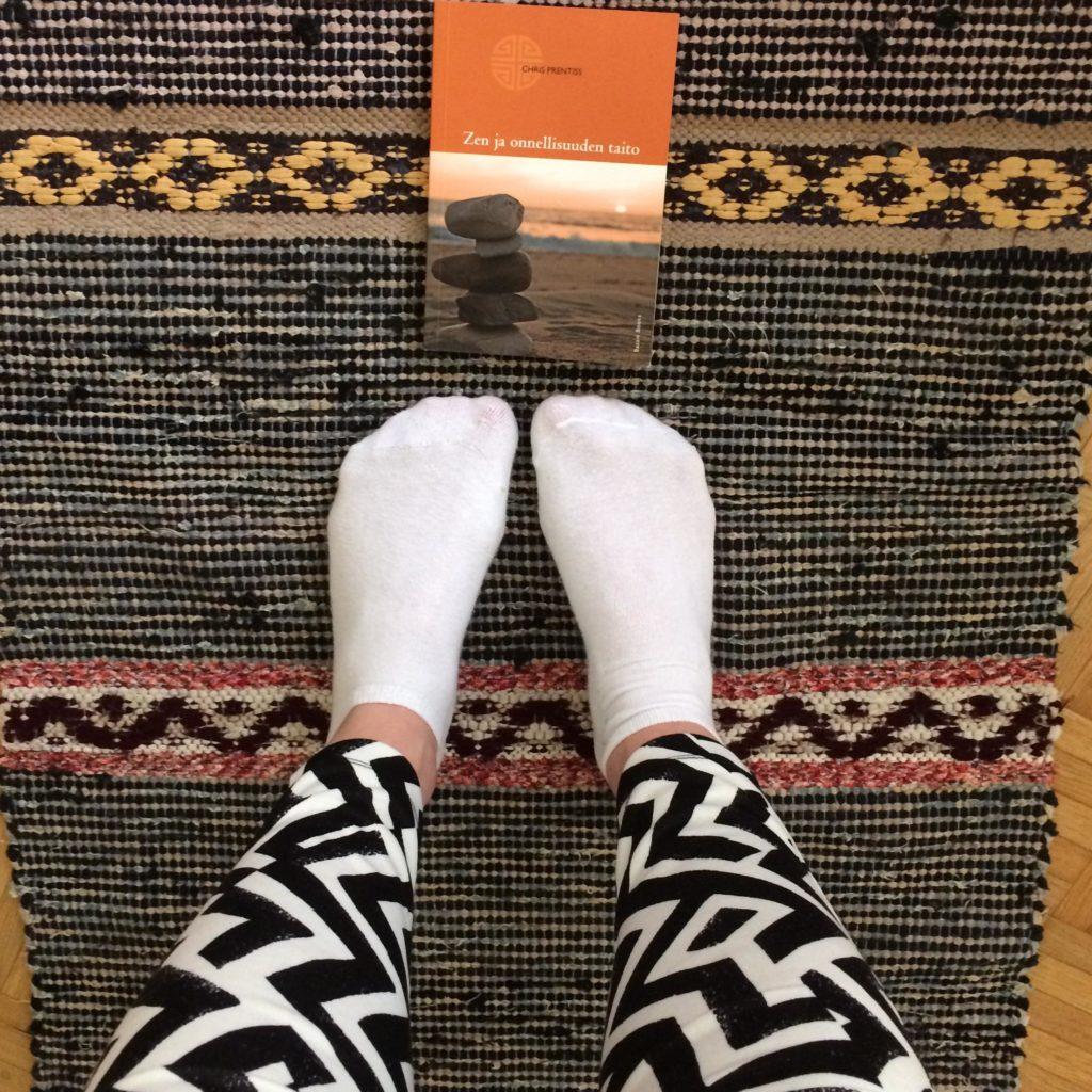 Kirja ja minä 7 euron leggingseissä anopin äidin kutomalla ikivanhalla matolla.
